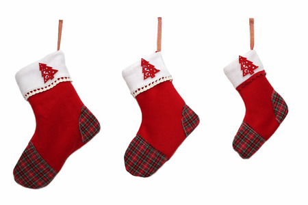 Three red Christmas socks with tree decor for Santa gifts on white background, winter holidays symbol