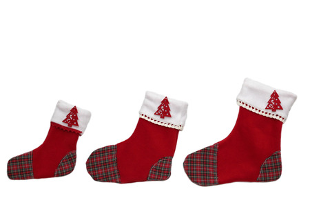 Three red Christmas socks with tree decor for Santa gifts arranged in order from smaller to bigger on white background, winter holidays symbol