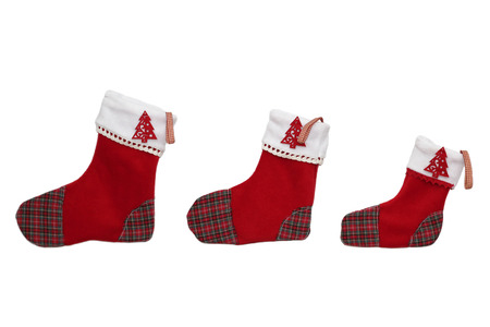 Three red Christmas socks with tree decor for Santa gifts arranged in order from bigger to smaller on white background, winter holidays symbol Stock Photo