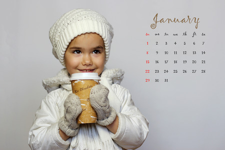 calendar date: January 2017 calendar with cute little girl holding mug and drinking tea in white coat, white knitted hats, scarves and mittens over white background, winter holiday concept