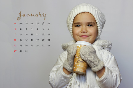 clothes organizer: January 2017 calendar with cute little girl holding mug and drinking tea in white coat, white knitted hats, scarves and mittens over white background, winter holiday concept