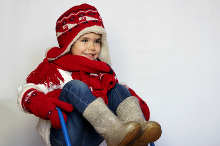 scarves: Cute little girl wearing red knitted hat, scarves and mittens on the sled over white background, winter activity concept Archivio Fotografico