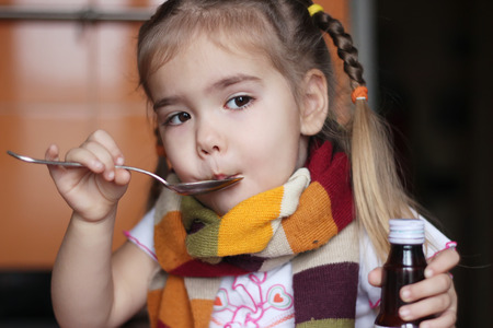 sniffles: Young sad child (girl) in the scarf keeping a spoon with liquid syrup and mixture for flu, indoor portrait
