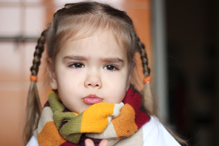 one child: Sad young child (girl) with sick look in the scarf on her throat, indoor portrait