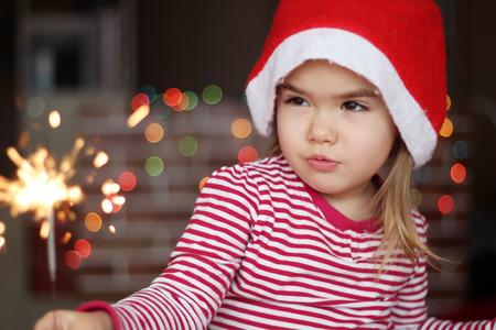éxtasis: La pequeña muchacha feliz en el sombrero de Santa entrecierra los ojos con malicia en la quema de bengala en la mano sobre fondo de Navidad Foto de archivo