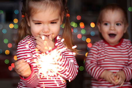 Handsome toddler boy and cute small girl in Santa hat hold burning sparkler and smile happily over defocused Christmas background