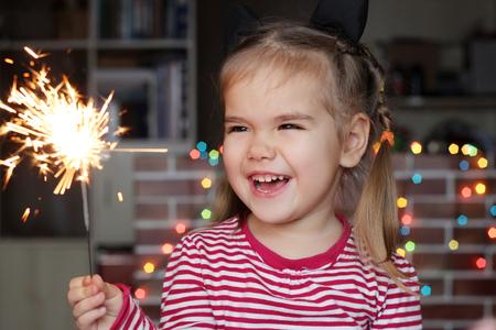 éxtasis: La pequeña muchacha feliz que mira con admiración en la quema de bengala en la mano sobre fondo de Navidad Foto de archivo