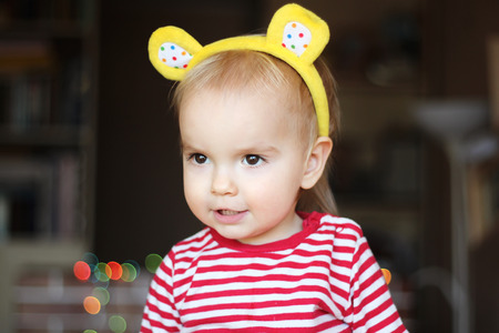 Close-up portrait of happy toddler boy with teddy bear ears looking inspired, human emotions Stock Photo