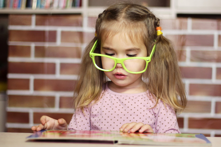 Portrait of a pretty child girl in funny green eyeglasses sitting at the desk and reading a book, indoor education concept