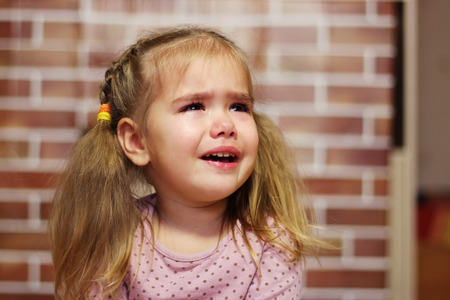 hysterics: Portrait of crying child girl, indoor portrait Stock Photo