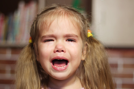 disobedient child: Portrait of crying child girl, indoor portrait Stock Photo
