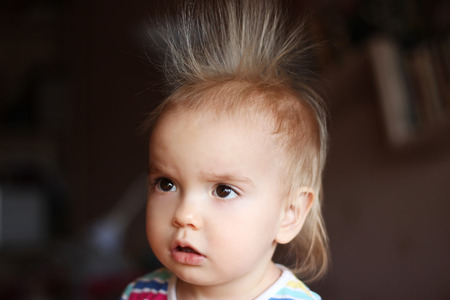 stood: Surprised cute child (boy) with fun face and hair stood on end, indoor portrait
