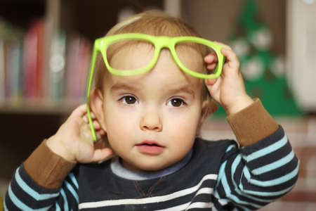 Funny kid boy with green eyeglasses, indoor portrait Stock Photo