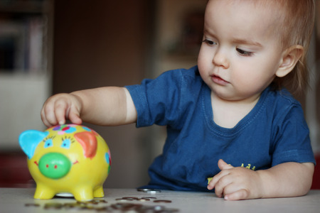 inserting: Baby boy inserting a coin into a piggybank, indoor financial concept