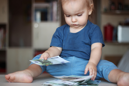 toddler boy: Toddler boy counting a denomination (paper notes) among wad of money, indoor financial concept