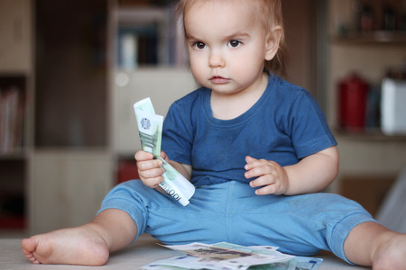 Toddler boy squeezes a denomination (paper note) sitting among wad of money, indoor financial concept