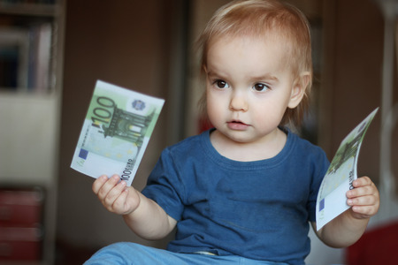 frugal: Toddler boy thinking to choose between two denominations (money), indoor financial concept Stock Photo