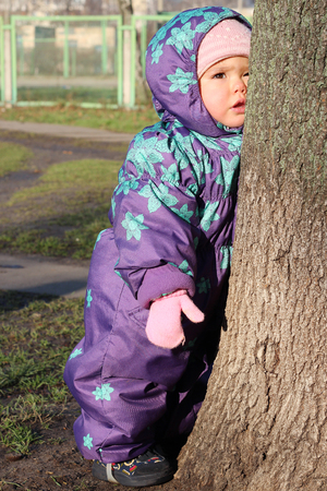 Tired cute toddler girl in the overall leaning on tree with her cheek, sunny winter outdoor Stock Photo