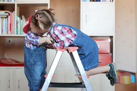 remount: Pretty child girl whispering something to her little toddler brother, both wearing in jeans overalls and standing on the step ladder, indoor building concept