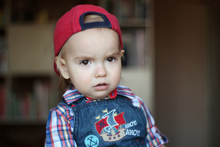 remount: Handsome toddler boy looks seriously wearing in jeans overalls and a red cap, indoor portrait, building concept