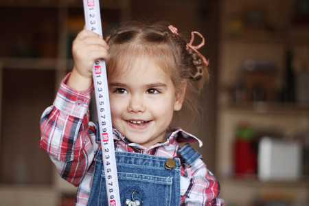 draftsman: Pretty child girl wearing in jeans overalls holds a measuring tape in her hands, indoor portrait, building concept