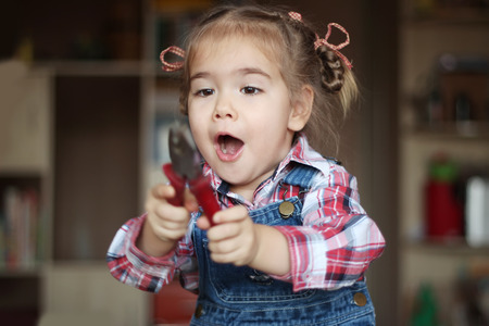 remount: Pretty child girl wearing in jeans overalls holds flat nose pliers and works with inspiration, indoor portrait, building concept