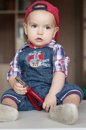 remount: Serious toddler boy wearing in jeans overalls and a red cap holds flat nose pliers, indoor portrait, building concept