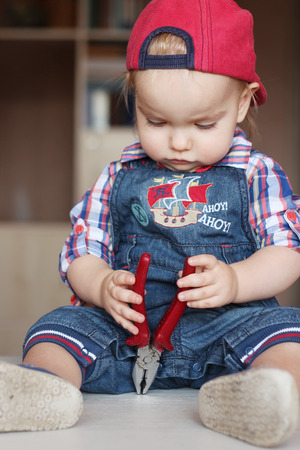 remount: Serious toddler boy wearing in jeans overalls and a red cap works with flat nose pliers, indoor portrait, building concept Stock Photo