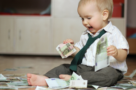 Inspired toddler boy wearing in a white shirt with a green tie and sitting among scattered paper money holds two hundred Euro denominations, business concept, indoor portrait
