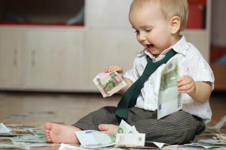 éxtasis: Inspirado niño pequeño que llevaba una camisa blanca con una corbata verde y sentado en medio de los billetes esparcidos tiene dos denominaciones de cien euros, concepto de negocio, retrato de interior Foto de archivo
