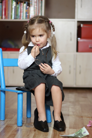 Little child girl wearing in grey business style dress takes off big black shoes with heels and bites an ear of eye-glasses