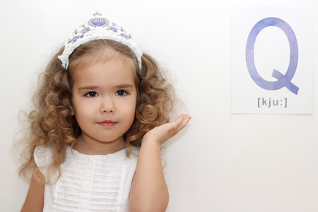 Pretty small girl with Q letter on white background adjusting her hair, indoor portrait
