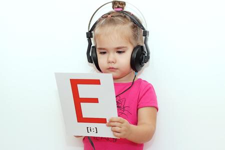 e pretty: Pretty small girl in the earphones reading a sheet of paper with E letter like printed music over white background, indoor portrait Stock Photo