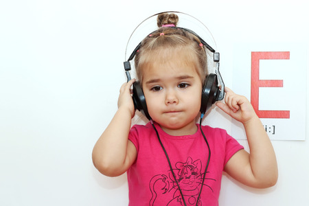 e pretty: Pretty small girl in the earphones listening to music over white background with E letter on it, indoor portrait Stock Photo
