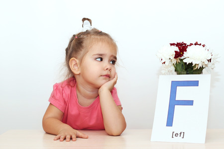 Pretty small girl looking on the bunch of flowers and picture with F letter over white background, indoor portrait