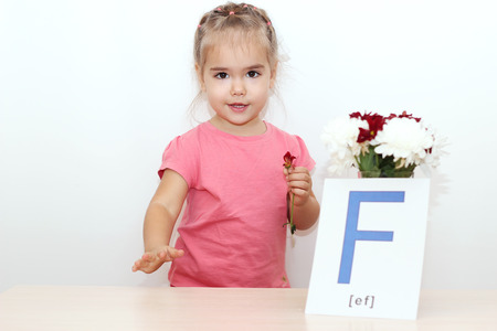 foretaste: Pretty small girl standing near the bunch of flowers and picture with F letter over white background, indoor portrait