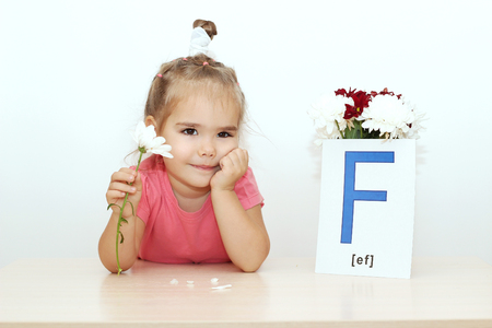 Pretty small girl telling fortunes with flower near the bouquet and picture with F letter over white background, indoor portrait Stock Photo