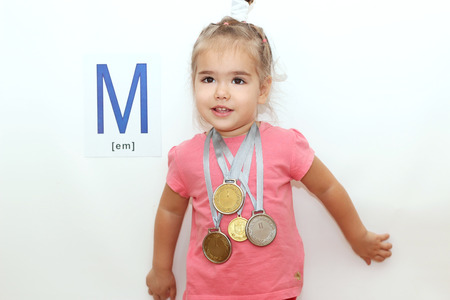 Pretty small girl with several medals on her neck over white background with M letter on it, indoor portrait Stock Photo