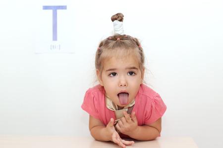 Mooi klein meisje vermoeid een gelijkspel steken haar tong uit op een witte achtergrond met T brief op het, indoor portret Stockfoto