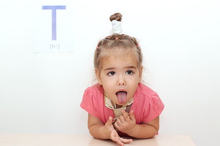 Pretty small girl wearied a tie sticking her tongue out over white background with T letter on it, indoor portrait