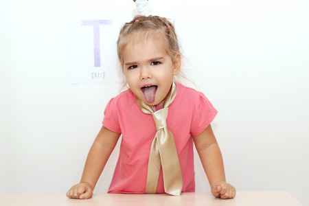 wearied: Pretty small girl wearied a tie sticking her tongue out over white background with T letter on it, indoor portrait