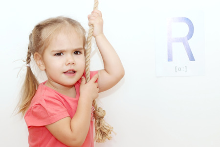 plaits: Pretty small girl with plaits pulling a rope over white background with R letter on it, indoor portrait, ABC concept