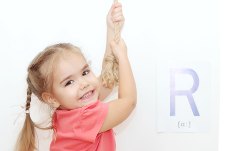 Pretty small girl with plaits pulling a rope and looking up over white background with R letter on it, indoor portrait, ABC concept