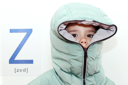 Pretty small girl wearing a hood of the winter coat with zipper over white background with Z letter on it, indoor portrait, ABC concept