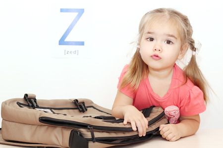 Pretty small girl opening a bag with zipper over white background with Z letter on it, indoor portrait, ABC concept Stock Photo