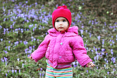 Little baby girl among first spring flowers, outdoor portrait Stock Photo