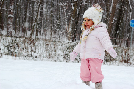 Happy toddler girl in warm coat and knitted hat tossing up snow and having a fun in the winter forest, outdoor portrait