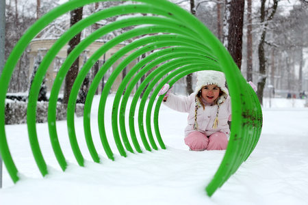 Happy toddler girl in warm coat and knitted hat looking playfully through the bicycle parking in the winter forest, outdoor portrait, winter family concept