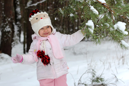 Happy toddler girl in warm coat and knitted hat shaking snow off the tree and having a fun in the winter forest on vacation, spending time outdoors
