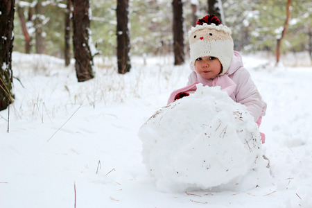 A little child girl sculpts snowman in winter landscape, winter concept, family spending time outdoors
